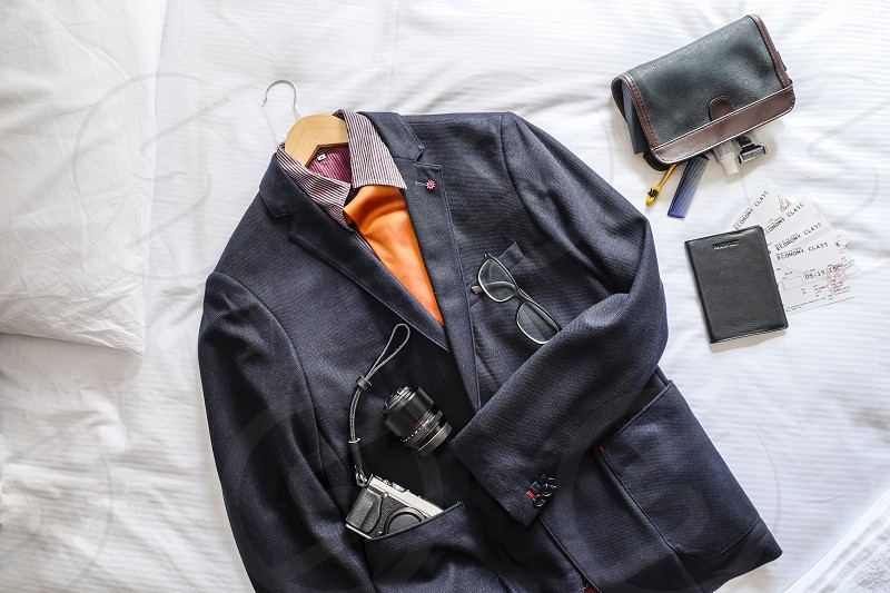 Overhead view of mens suit and travel essentials flat lay on bed photo