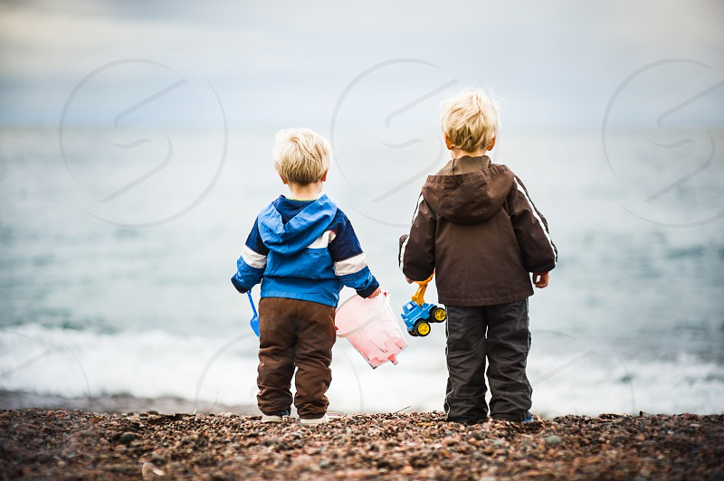 boys brothers youth beach cold playing water ocean lake rocks toys pail bucket truck loader scoop bulldozer shovel blue pink jackets blonde waves sky tide watching waiting wonder kids fun vacation powerful curious hesitant photo