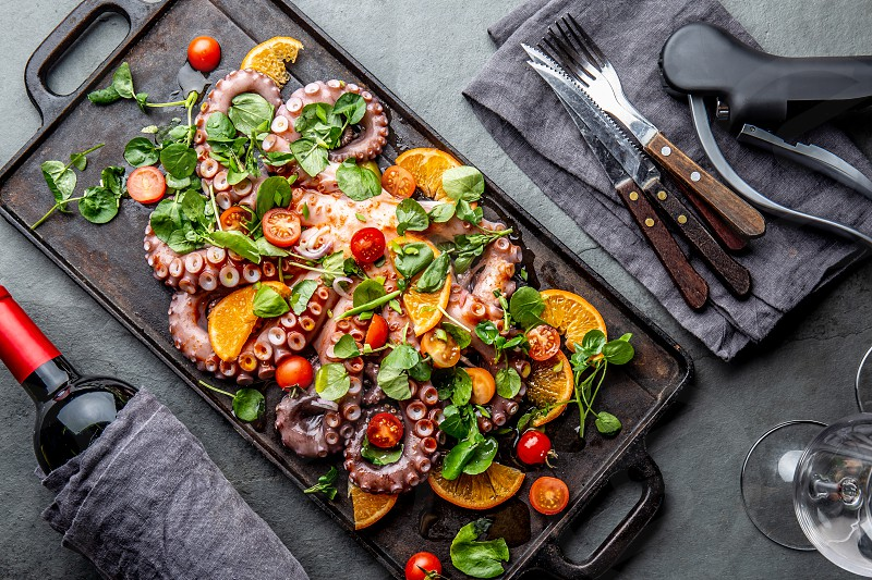 Whole octopus salad with orange tomatoes and cress salad served on board with wine. photo