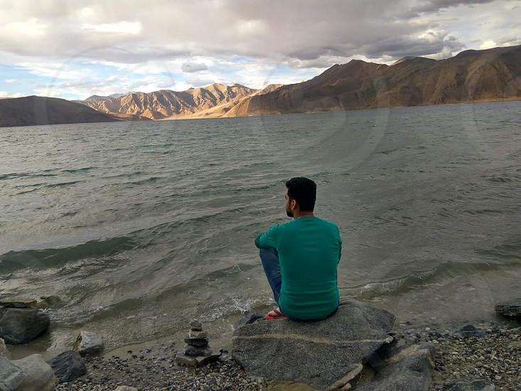 Remincing lake thoughts thinking beautiful admiring mountains sunlight clouds view nature stone shore watching shot photo