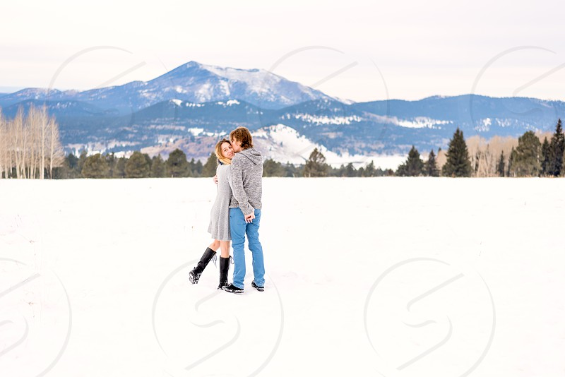 Engagement photos couple playing in the snow near Christmas time - Flagstaff Arizona photo