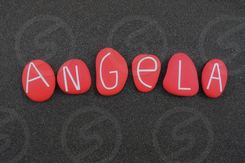 Angela female given name composed with red colored and carved stone letters over black volcanic sand photo