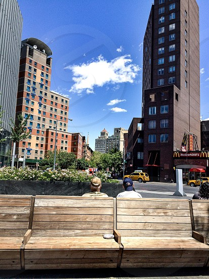 two men sitting on brown bench in front of high rise buildings photo