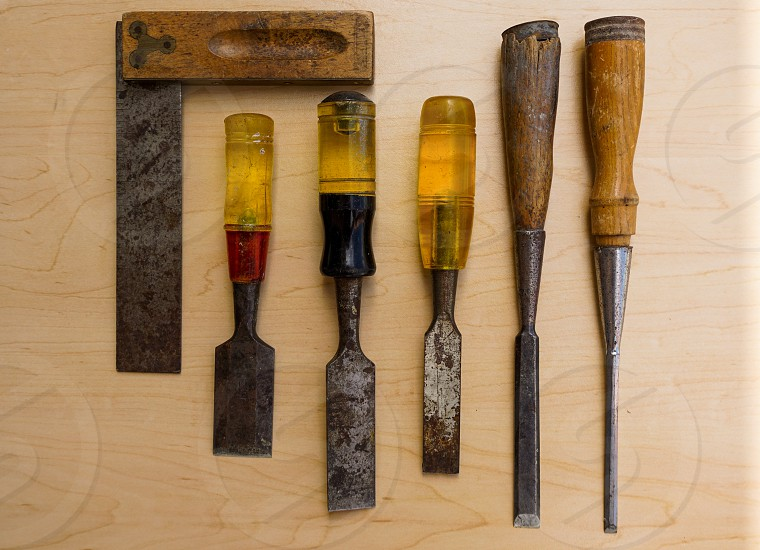 A still life of old antique carpentry tools including chisels and and a wood and steel measuring square photo