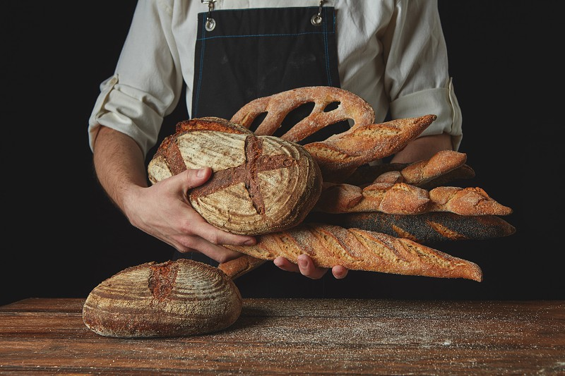 Men's hands hold many different breadson a wooden table photo