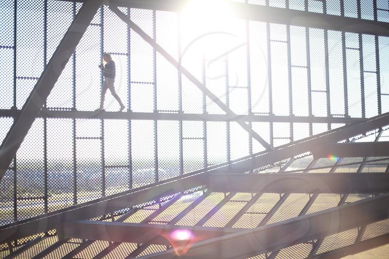 man walking on gray metal photo