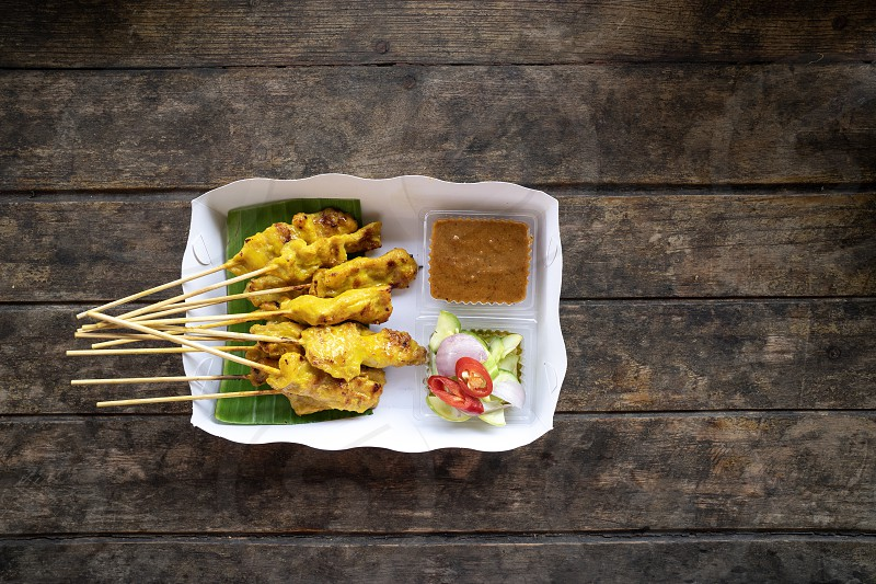 top view delicious pork satay skewers with peanut dipping suace and sider in white paper box on wooden table one of famous street food Thai local dishes. photo