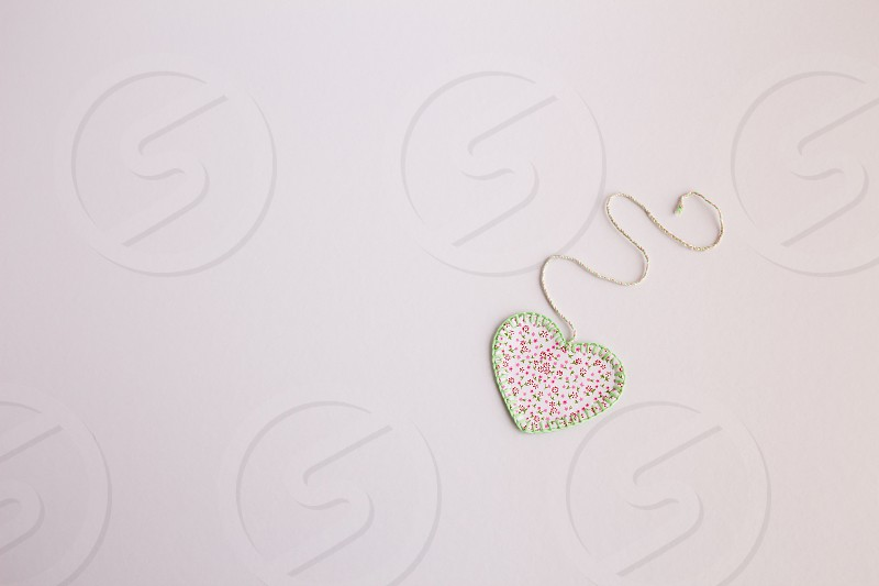 Heart-shaped cloth patch on white background. photo