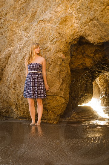 woman in black and white tube top midi dress standing in front of brown cave rock photo