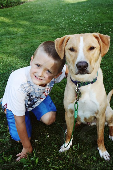 A boy and his dog love in the summer and outside photo