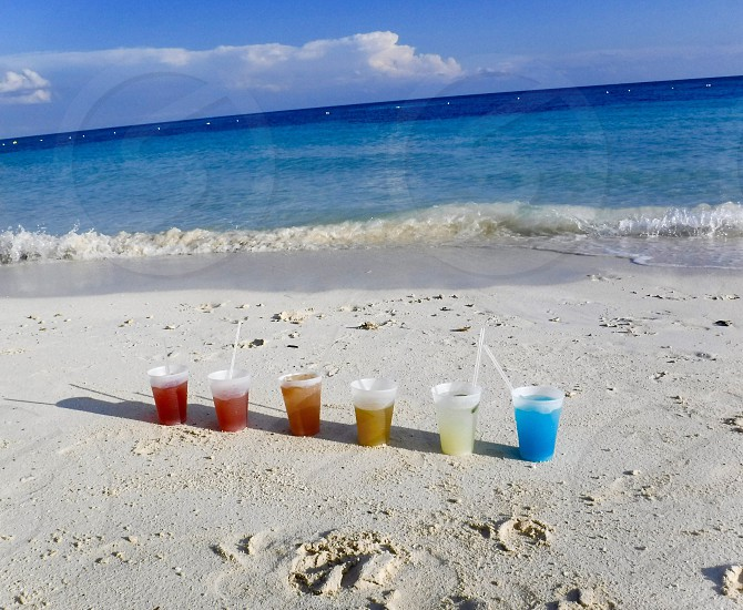 Bahamas beach cocktail alcohol sand colorful rainbow relax ocean sun sunny day. Destination travel photo