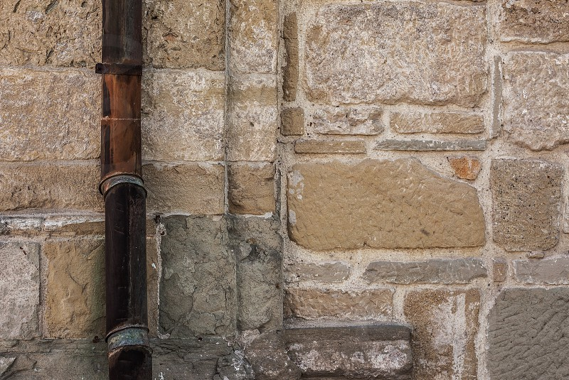 Details of an old stone wall obsolete architectural style and old gutter. photo