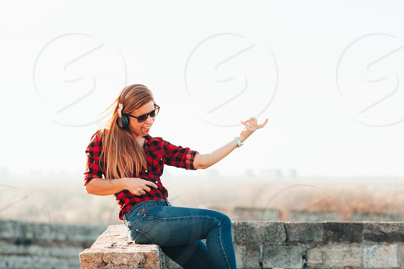 Young woman listening to the music on headphones playing imaginary guitar outdoors photo