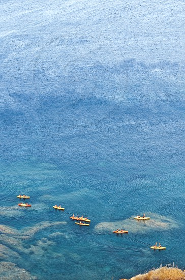 a group of people riding a kayak strolling near the coast of Cabo de Gata Andalusia in the blue and crystalline waters of the Mediterranean sea. Panoramic photo