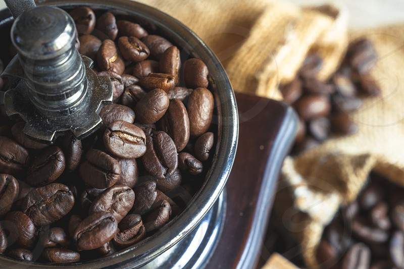 close up coffee beans in vintage wooden mill-grinder photo