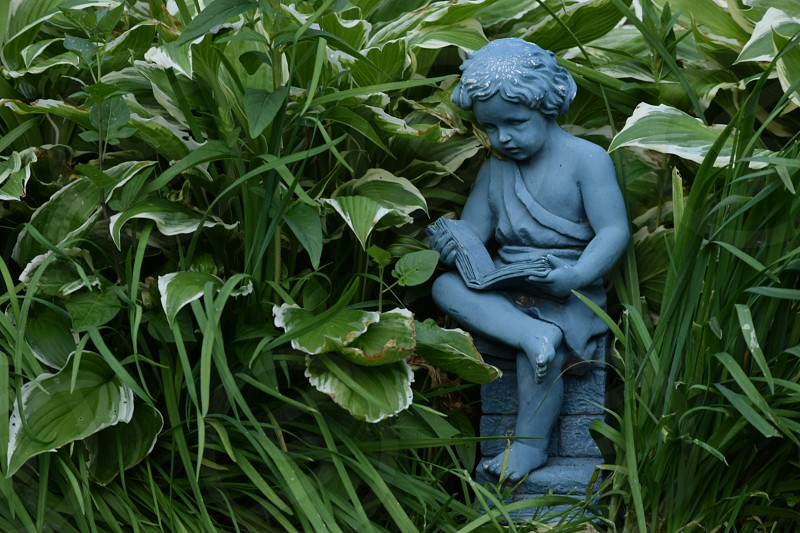 garden statue of child reading photo