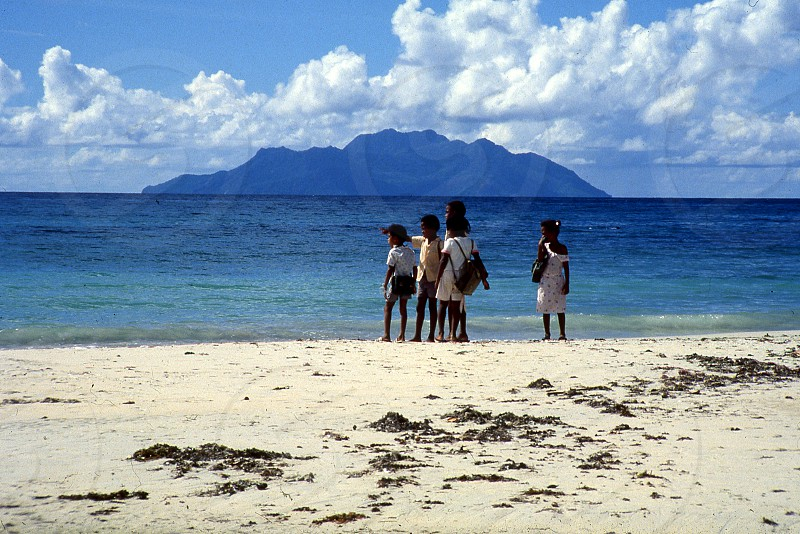 Kids walking home from school on the beach photo