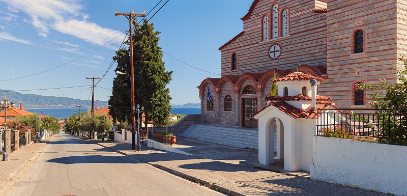 Stavros Greece - September 04 2017: Big Orthodox church on hill with view on main street sea and surroundings.  photo