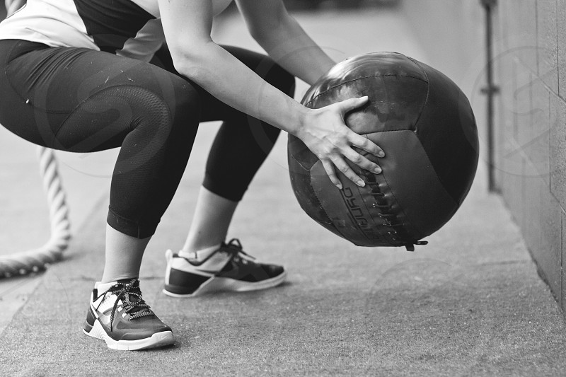 woman in gym outfit holding fitness ball in both hands bending knees posiion photo