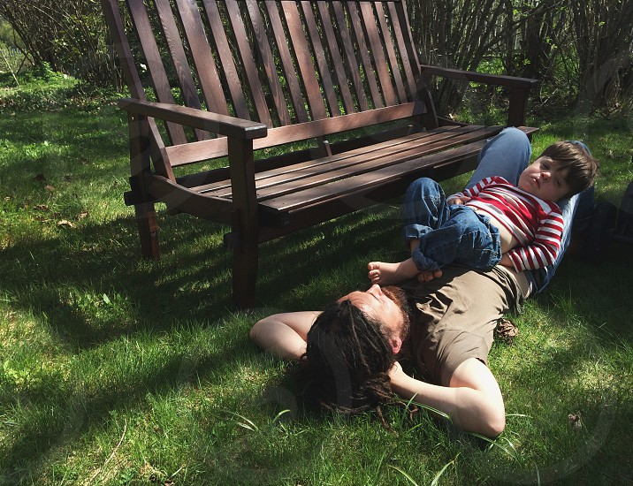 father and son lying in the grass photo