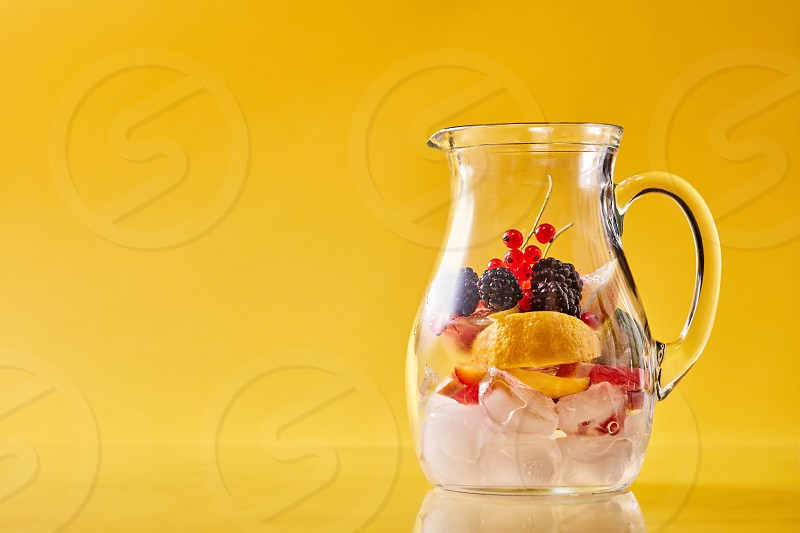 Preparation of homemade refreshing cold fruit punch in a glass jar on an yellow background copy space. Concept of cold nonalcoholic summer drinks. photo