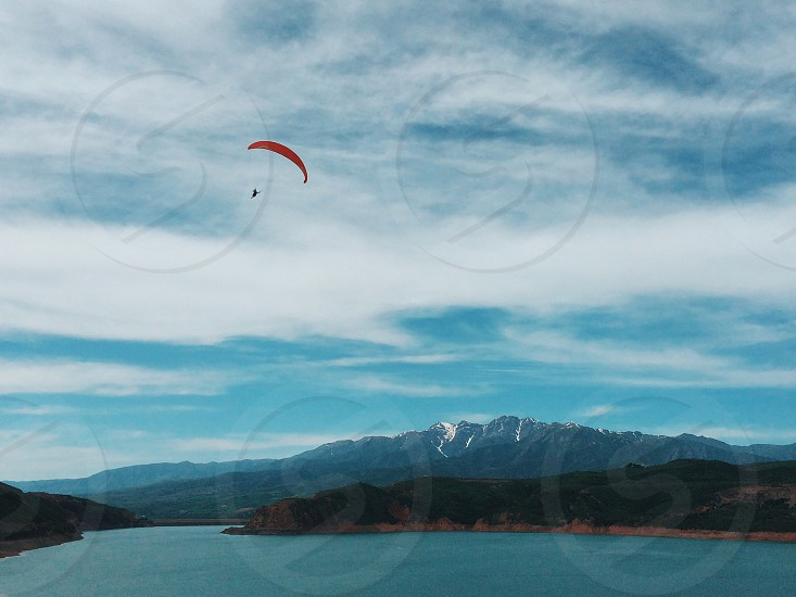person paragliding above lake during daytime photo