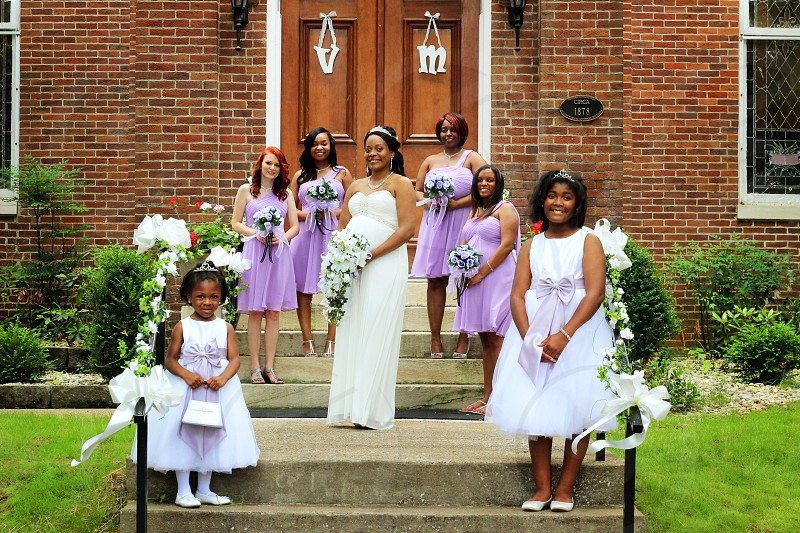 girls wearing white dress and purple tube dress holding bouquet in front of brown concrete building photo