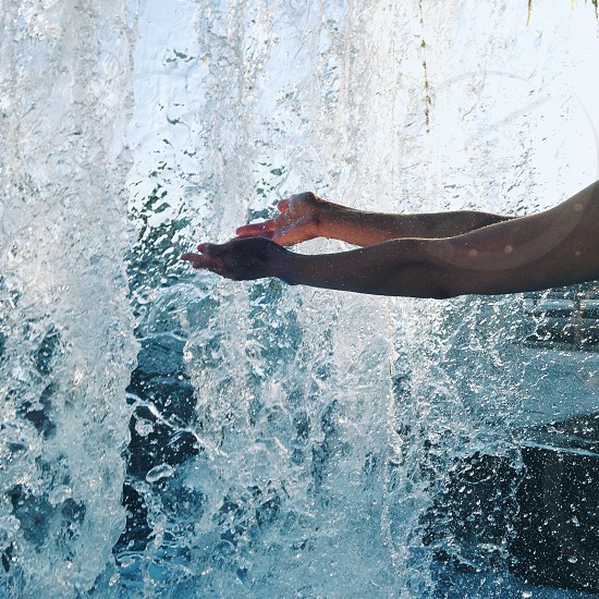 person putting hands under falling water photo