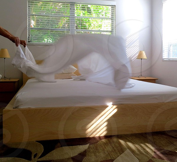 Clean sheet billowing onto bed on laundry day photo