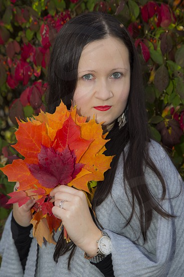 woman in gray poncho holding red and orange maple leaf near red and green leaf plants photo