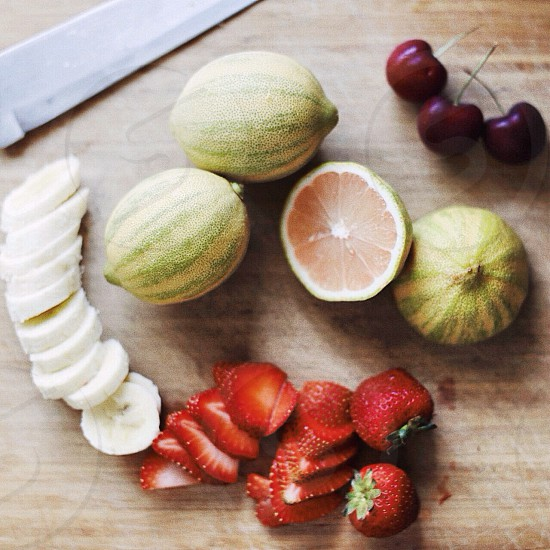 sliced strawberries and bananas beside cherries photo