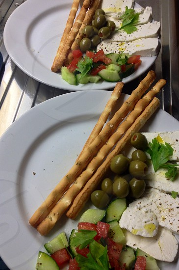 4 stick breads olive greens parsleys white cheese sliced tomatoes and sliced cucumbers on 2 white ceramic plates photo
