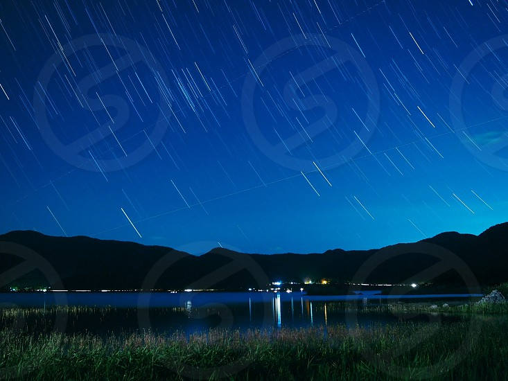 green grass field near body of water under blue sky with shooting star illustration photo