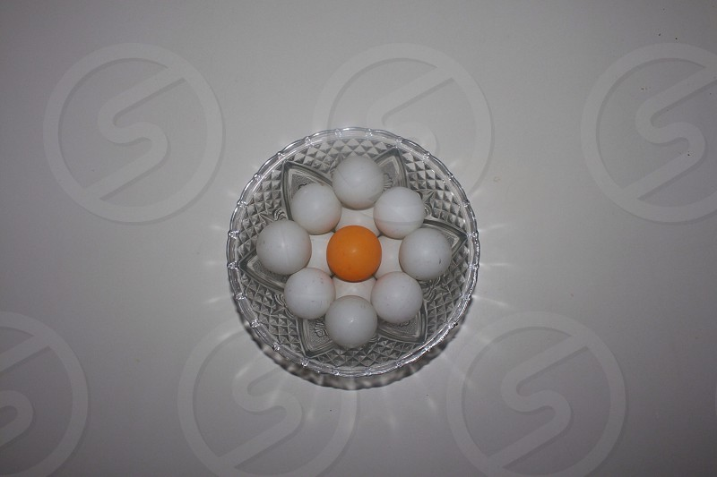 glass bowl with 8 white balls and 1 orange ball photo