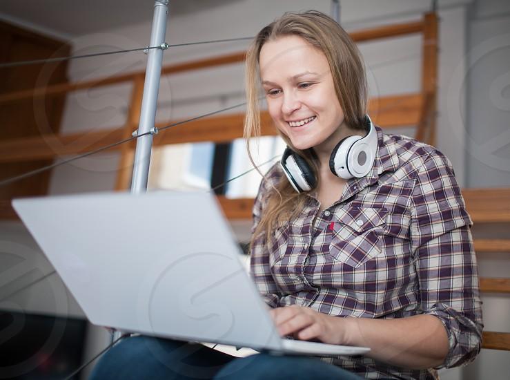 Young happy woman with headphones on the neck entertaining herself with laptop sitting on the stairs at home photo