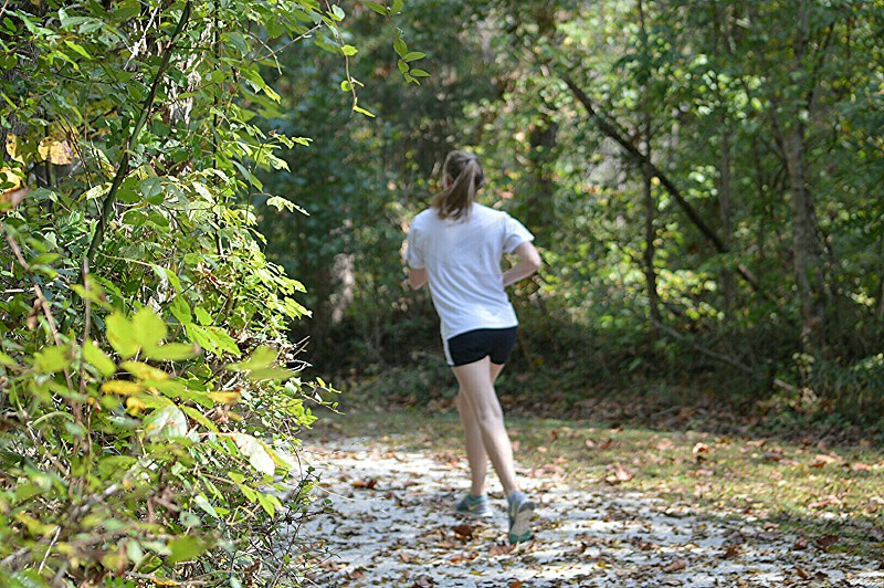 woman in white t shirt jogging on pathway between green trees photo