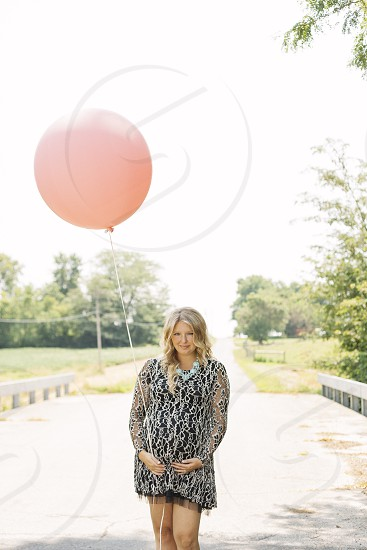 woman holding pink balloon with hands on stomach photo