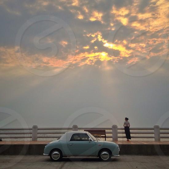 woman standing near grey convertible car photo