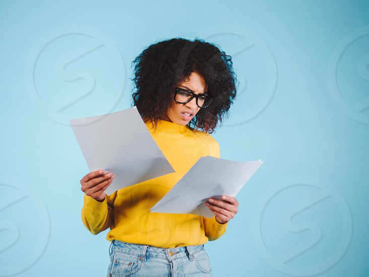 Worried african american businesswoman reading a notification standing on blue background in yellow wear and afro hairstyle. photo