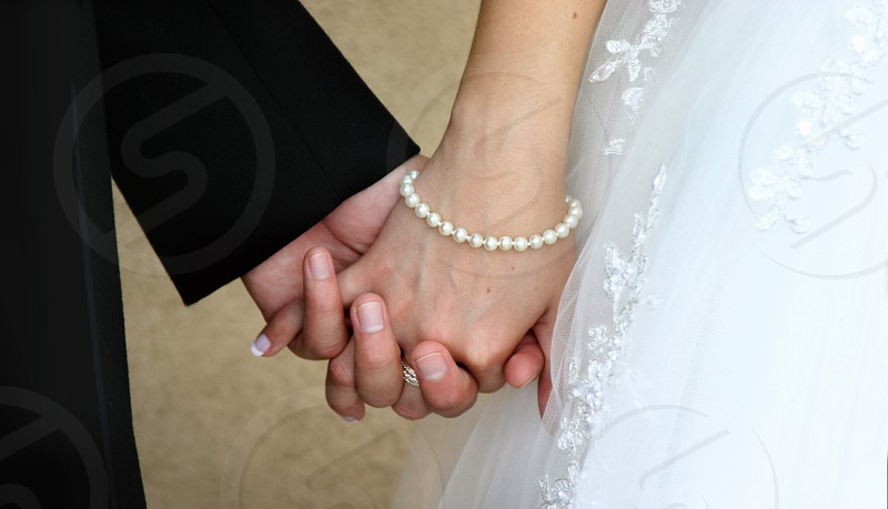 A bride wearing a white gown and pearl bracelet holds hands with a groom in a tuxedo.  photo