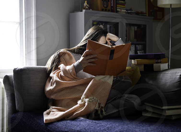 Teenage girl reading a book whilst relaxing on the sofa. photo