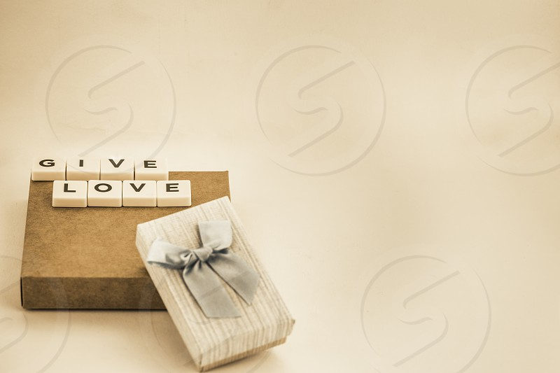 Conceptual photo of valentine's day gift box with blue bow and the phrase give love with copy space pink background photo