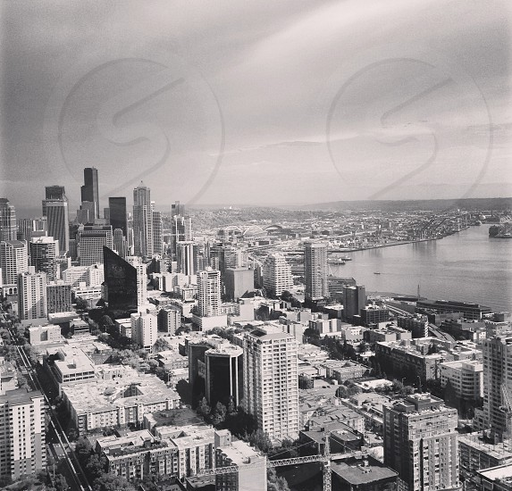 Black and white photo of city landscape next to a body of water. Taken from the top of the Space Needle in Seattle WA.  photo