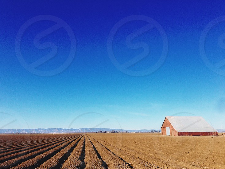 red barn house on brown farm field under blue sky photo