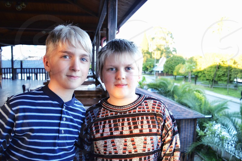 boy wearing blue and white stripe polo shirt beside other boy wearing brown and gray sweater during daytime photo