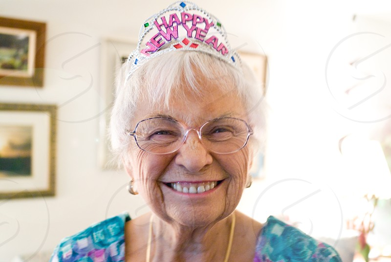 smiling woman wearing a happy new year hat and blue top photo