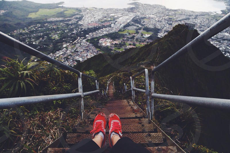 person wearing red and white shoes sitting on brown staircase  photo