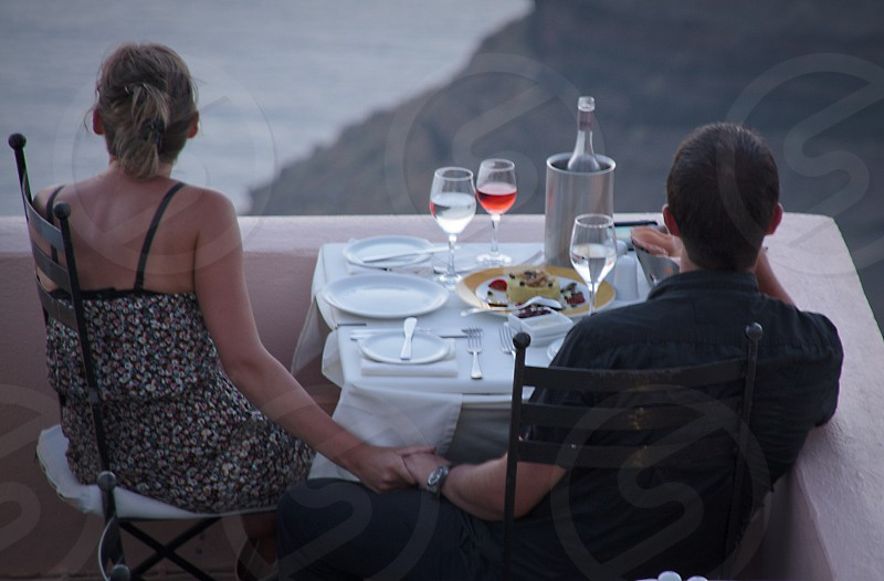 Couple eating al fresco at a cliffside restaurant photo