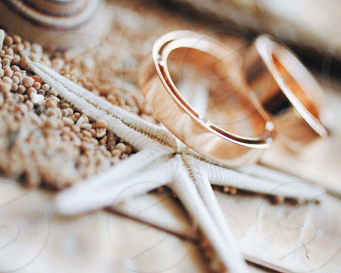 close up photo of rose gold rings on white starfish and pebbles photo