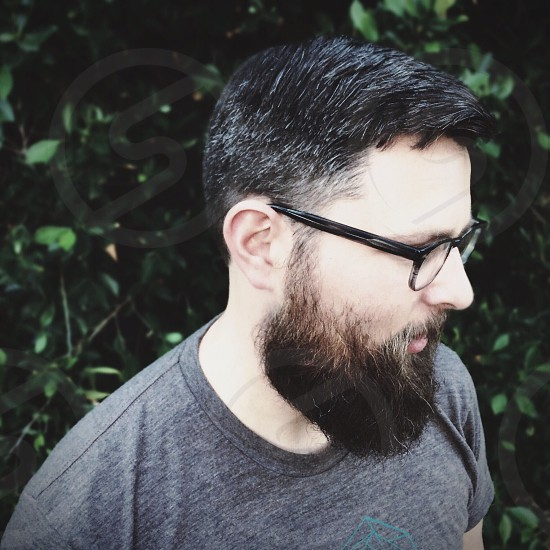 man in grey crew neck t shirt black plastic glasses with beard looking down near green foliage photo